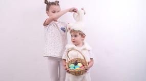 Syskongruppen firar påsk Pojken är iklädd en kanindräkt och rymmer en korunzku med påskägg royaltyfri foto