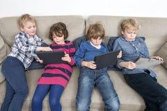 Syskongrupper Using Digital Tablets på soffan Royaltyfri Fotografi