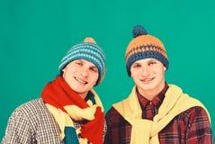 Syskonställningsslut och leende Grabbar i stack scarves arkivfoton