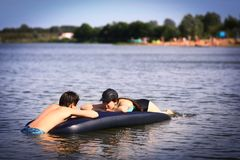 Syskonsyskongruppen med uppblåsbara matrass simmar i sjön på sandstrandbakgrund arkivfoto