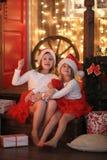 Syskonsystrar i santa hattar med dockan nära spisen på Chri fotografering för bildbyråer