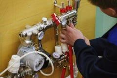 Système de chauffage rayonnant d'installation de chauffage par le sol L'homme installent la construction de plancher sous le plan photo libre de droits