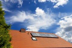 Système de chauffage solaire de l'eau sur le toit rouge avec le ciel bleu - panneaux de Gelio Images libres de droits