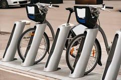 Système de location de vélo de ville Les pièces de bicyclette sont grandes Bicyclettes de stationnement sur des rues de ville Ave Photographie stock