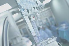 Systèmes médicaux de l'égouttement IV sur un fond de la salle d'opération images libres de droits