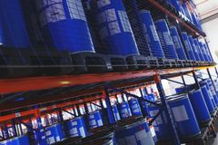 System of address storage of products, materials and goods in a warehouse. blue plastic barrels for storage of chemical liquids. System of address storage of Royalty Free Stock Photo