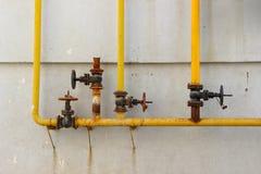 System der alten Gasregelventile und der Gasrohre auf der Wand Stockfoto