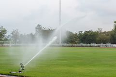 System working on fresh green grass on football or soccer stadium. Sprinkler watering field football. royalty free stock images