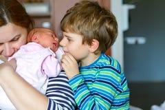 Syster för pojke för liten unge kyssande nyfödd Moderinnehavet behandla som ett barn på armen Royaltyfri Fotografi