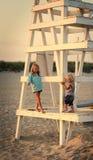 Syster och broder på stranden under solnedgång Arkivbild