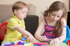 Syster och broder som hemma spelar Arkivbild