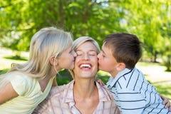 Syster och broder som kysser deras moder Royaltyfri Foto