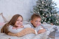 Syster och broder som ligger på säng Royaltyfria Foton