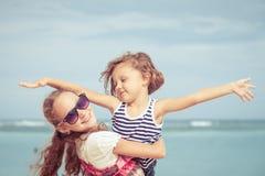 Syster och broder som spelar på stranden på dagtiden Royaltyfri Foto