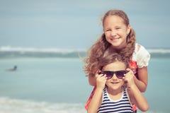 Syster och broder som spelar på stranden på dagtiden Fotografering för Bildbyråer