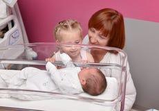 Syster- och farmorblickarna på ett nyfött behandla som ett barn i sjukhuset royaltyfria foton
