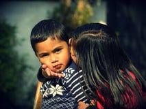 Syster som kysser henne broder Royaltyfri Foto