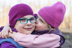 syster som kysser lovingly hennes äldre syster Arkivbild