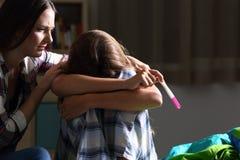 Syster som tröstar till ett gravid ledset tonårigt arkivbilder