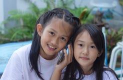 Syster som två är lycklig med en mobiltelefon royaltyfria bilder