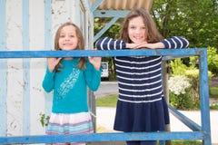 syster som två har gyckel i de gladlynta barnen för parkera som utomhus spelar, lycklig familjförälskelse för bästa vän och lycka royaltyfria bilder