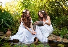 Systern häller vatten från en tillbringare i henne armflickan Fotografering för Bildbyråer