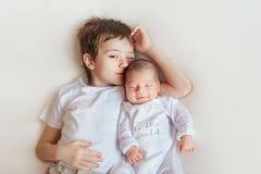 Systern och brodern Kids som sover behandla som ett barn, pojkebarnet och den nyfödda flickan på vit fotografering för bildbyråer