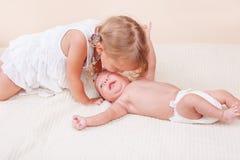 Systern som kysser henne, behandla som ett barn brodern Royaltyfri Foto