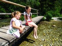 2 systers сидя над рекой Стоковое Фото