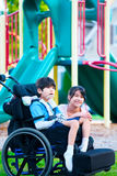 Systersammanträde bredvid rörelsehindrad broder i rullstol på playgroen Royaltyfria Bilder