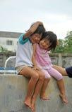 Systersmilimg för asiat två och huging Fotografering för Bildbyråer