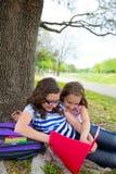 Systervänner som flickor kopplade av under träd, parkerar efter skola Arkivbild