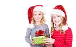 Systrar eller två unga flickor som bär jultomtenhattar Arkivfoton