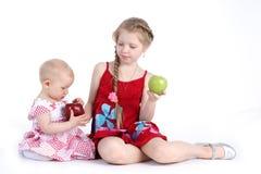 Systrar 8 gamla år och 11 månad med äpplet Arkivbilder