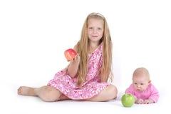 Systrar 8 gamla år och 11 månad med äpplet Royaltyfria Foton