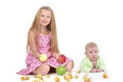 Systrar 8 gamla år och 11 månad med äpplet Royaltyfria Bilder
