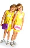 Systrar kopplar samman i gula klänningar Arkivfoton