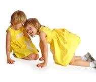 Systrar kopplar samman i gula klänningar Fotografering för Bildbyråer