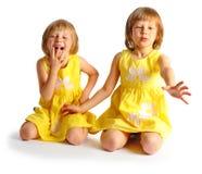 Systrar kopplar samman i gula klänningar Arkivbilder