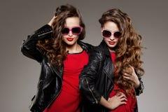 Systrar kopplar samman i hipstersolexponeringsglas som skrattar två modemodeller Fotografering för Bildbyråer
