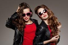 Systrar kopplar samman i hipstersolexponeringsglas som skrattar två modemodeller Arkivbild