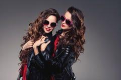 Systrar kopplar samman i hipstersolexponeringsglas som skrattar två modemodeller Royaltyfri Fotografi