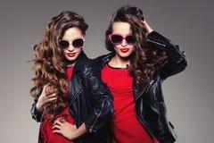 Systrar kopplar samman i hipstersolexponeringsglas som skrattar två modemodeller Royaltyfria Bilder