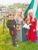 Systrar och broder i medeltida klänning på Portsoy Royaltyfria Bilder