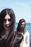 Systrar på stranden som kramar sig härligt ståendebarn Arkivbilder