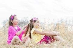 Systrar sitter i landsäng som flätar hår Fotografering för Bildbyråer