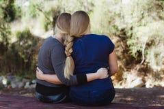 Systrar som kramar sig med långt hår, flätade togther Arkivfoton