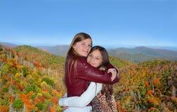 Systrar som kramar sig på en härlig höstdag Arkivbilder