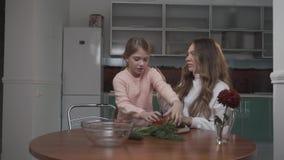 Systrar som lagar mat grönsaksallad på tabellen i köket Den mer unga systern kommer med tomater till den äldre systern lager videofilmer
