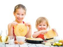 Systrar som lagar mat pannkakor Arkivfoto